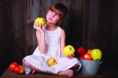 A young girl eating an apple next to a bucket of apples