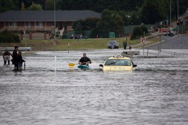 Flooded road with stranded taxi underwater and man paddling kayak on water