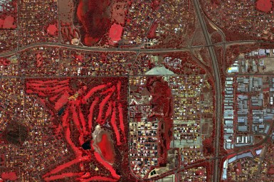 An aerial view of city streets and buildings with areas coloured in red