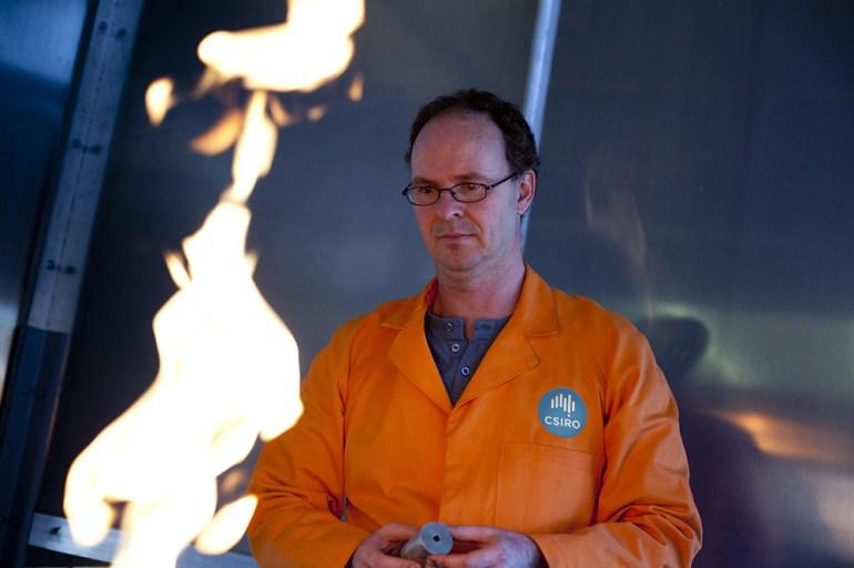 Man in orange coat looking at flame