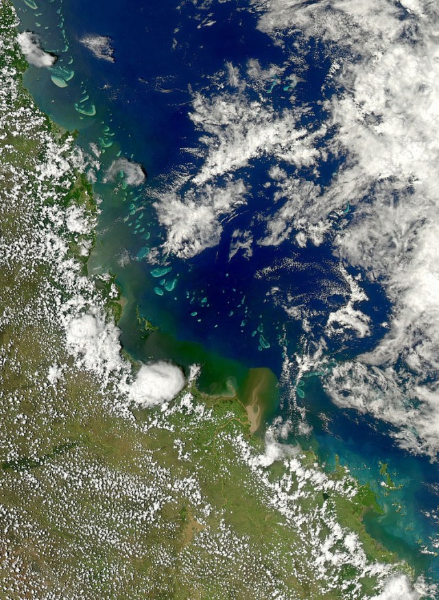 Queensland Coastline as seen from space shows the Great Barrier Reef and muddy water flowing from hte Burdekin River into the ocean.