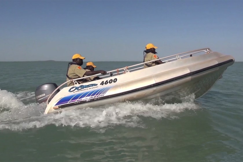 Three Indigenous rangers in a motor boat