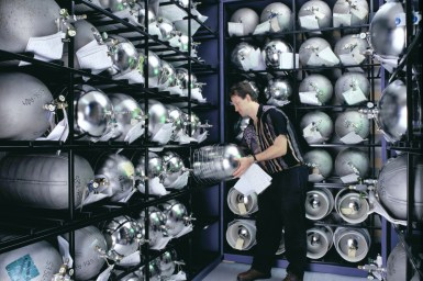man in a storage room with shelves of gas cylinders