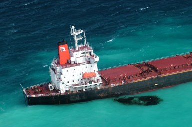 ship at sea with black oil spill in the water