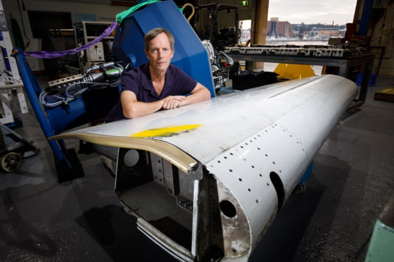 man leaning on a piece of airplane wing