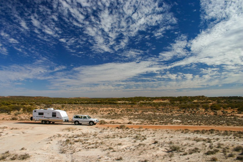 car and caravan driving on a dirt road with a blue sky and clouds