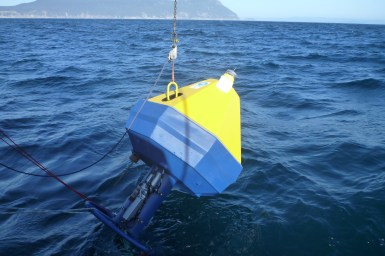 bright yellow and blue capsule being lowered into the ocean with an island in the distance