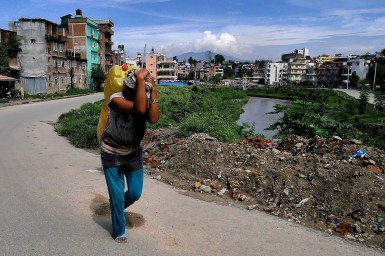 A woman carrying watre on her back from the Bagmati River in Nepal