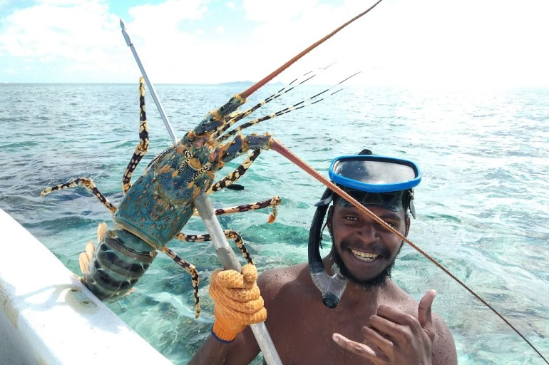 Indigenous fisher wearing snorkel on his head holding a rock lobster caught with a spearing device