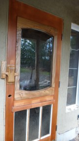 A recycled door cleaned up and turned upside down with new large window added, fished with elm trim scavenged from the firewood pile.