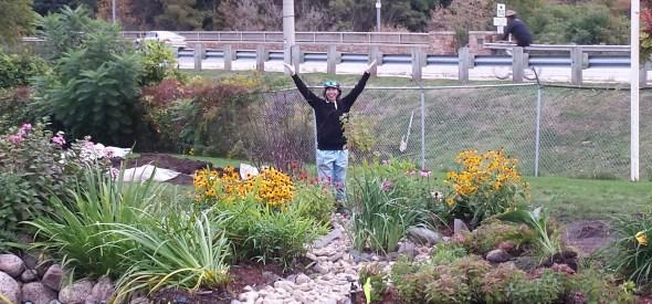 Volunteer posing with the completed rain garden.