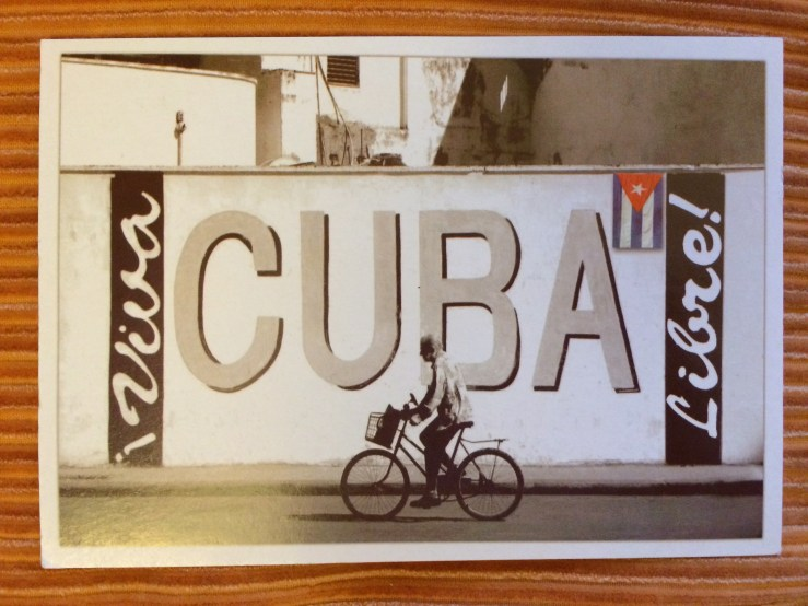 Postcard of a cyclist in front of a big Cuba sign