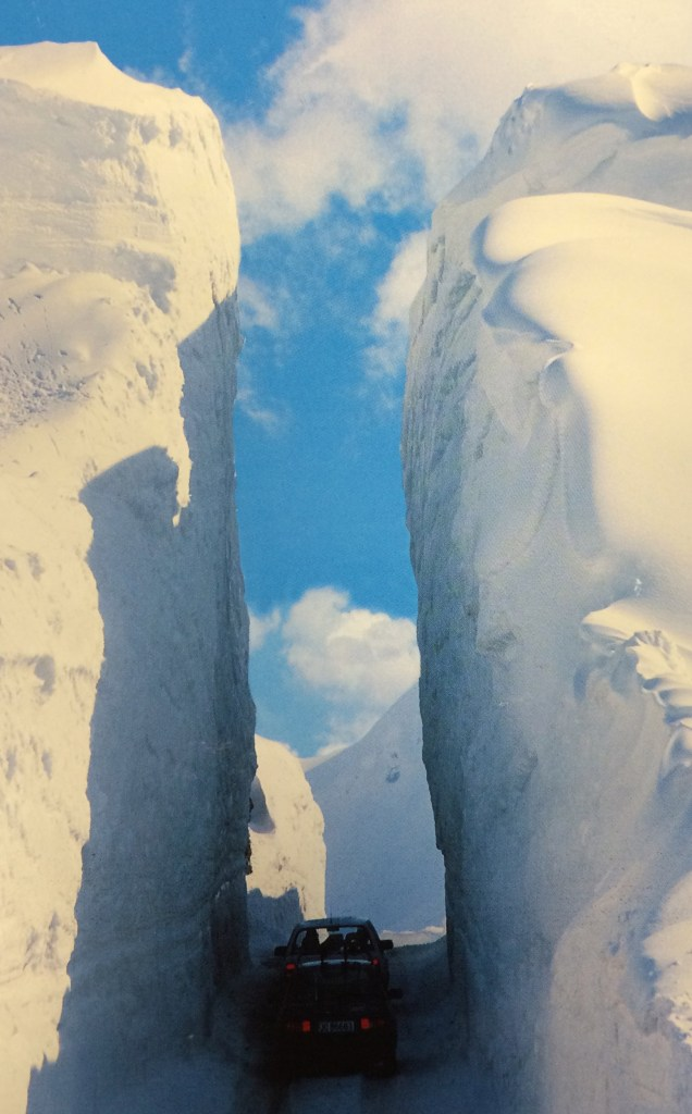 Postcard of very high snowbanks with a road cut through