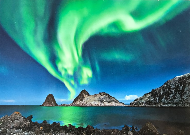 Image of swirly green northern lights over a fjord.