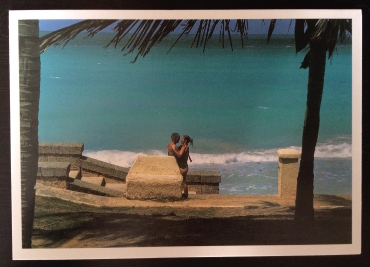 Image of a couple kissing in front of an idyllic blue sea