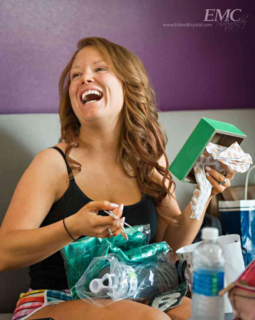 A bridesmaid laughs as she opens her present from the bride. Image by EMC Photography