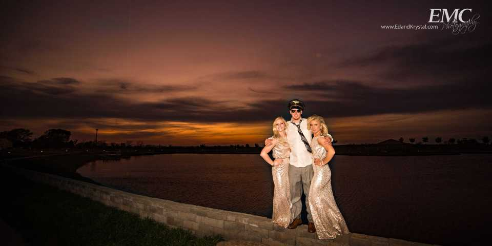 While the sun is setting in the background, two bridesmaids are hugged by a groomsmen, wearing a costume police cap.