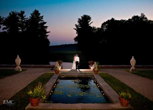 Bride and groom kiss at the far end of a koi pond at Allerton during sunset