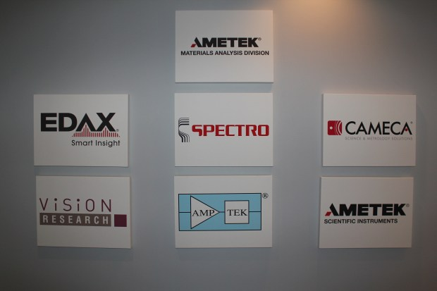 Canvas signs on the wall outside the demo labs in Mahwah, NJ showing some of the companies in the AMETEK Materials Analysis Division.