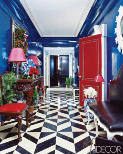 The gallery of a Manhattan home by Miles Redd features a bench by John Rosselli Antiques and Decorations and a leather-covered door trimmed with silver nailheads; the floor is painted in a faux-marble pattern, and the walls are lacquered Yves Klein-blue.