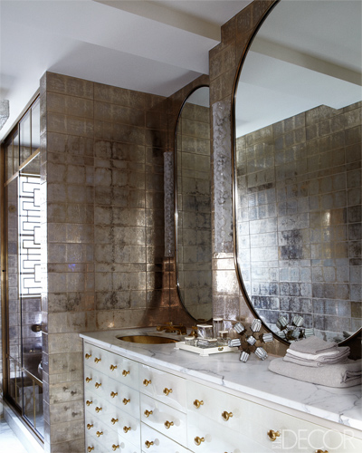 The master bath is sheathed in glass tiles by Ann Sacks, the parchment-covered vanity and mirrors are custom made, and the sink and fittings are by Waterworks. And see the full home tour here.