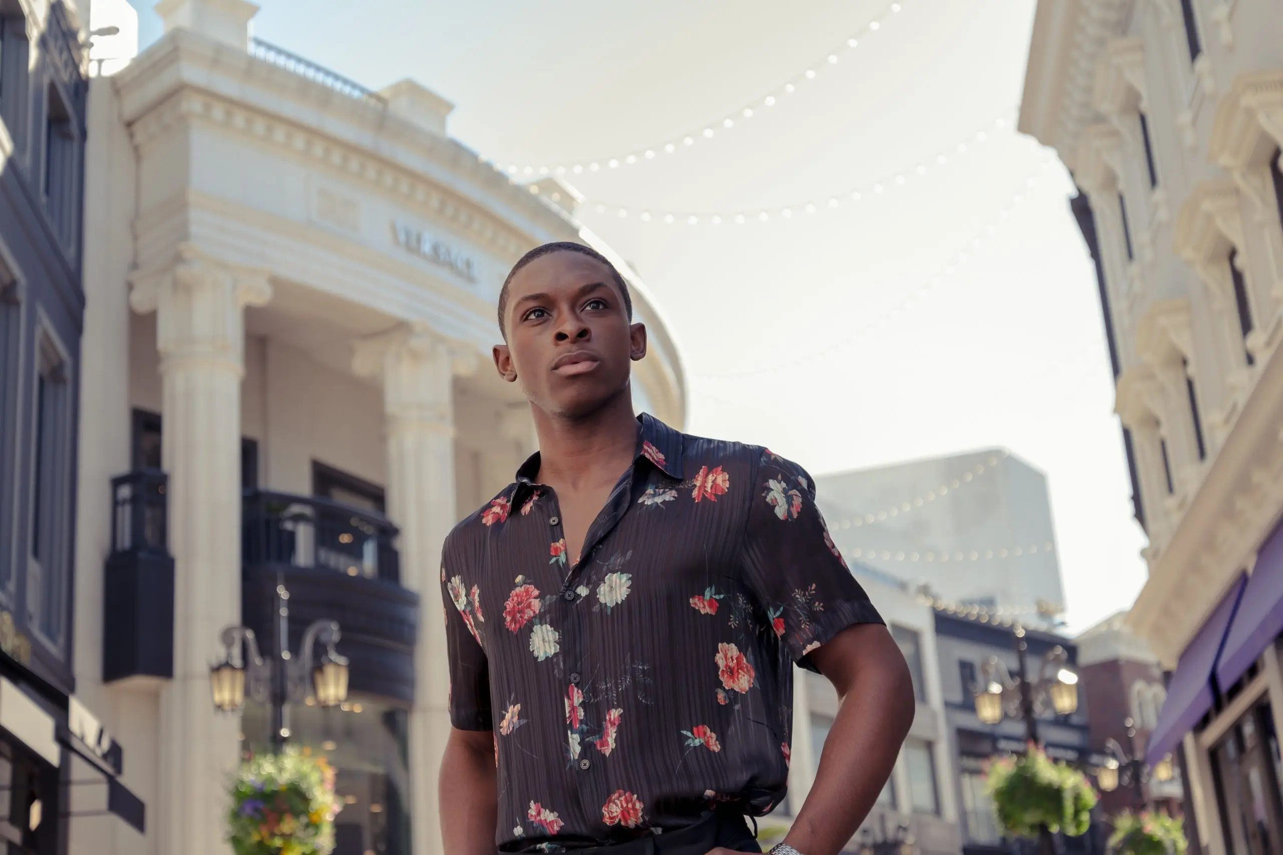 Black male model posing in front of the Versace building in Rodeo Drive in Beverly Hills, California wearing a black floral button-down shirt.