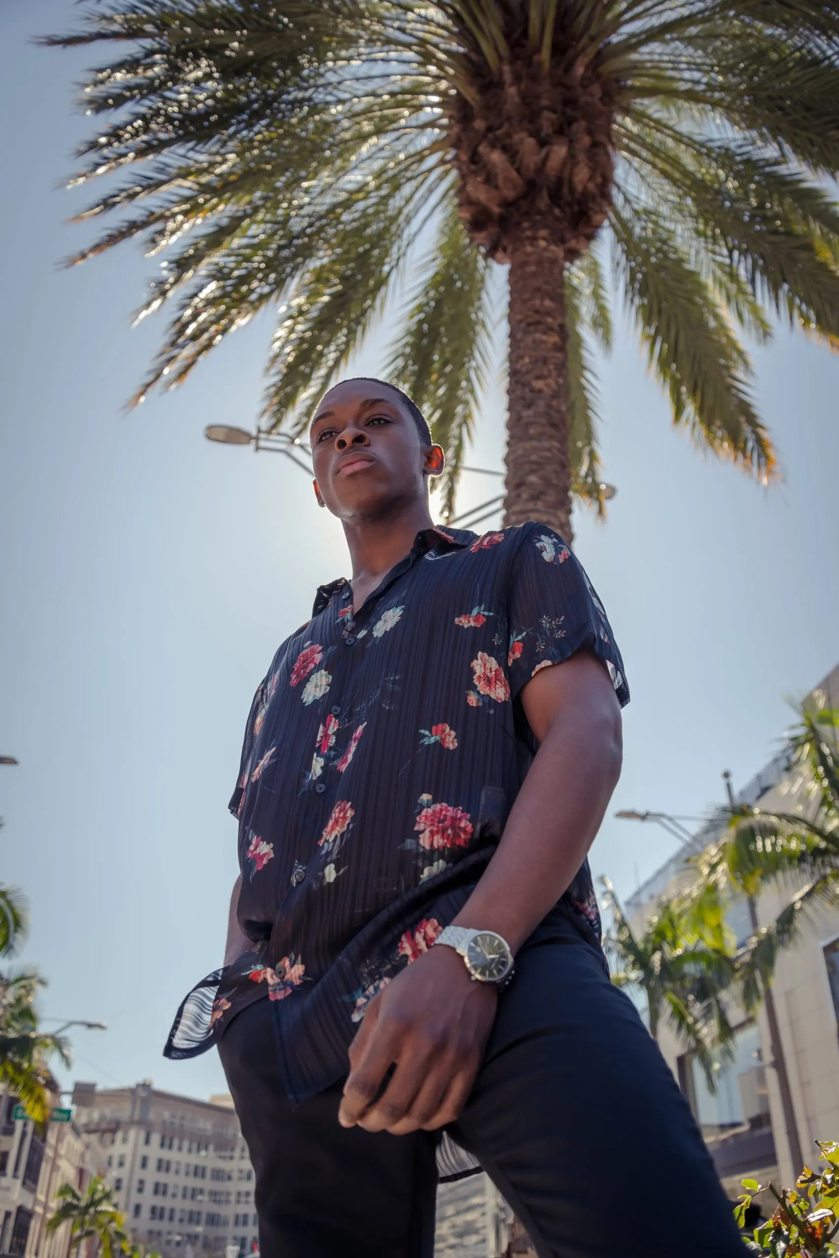 Black male model posing in front of California palm tree's and a light post sporting a black and floral button-down shirt and a nice watch.