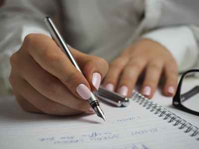 Pair Of Hands Writing In A Notebook