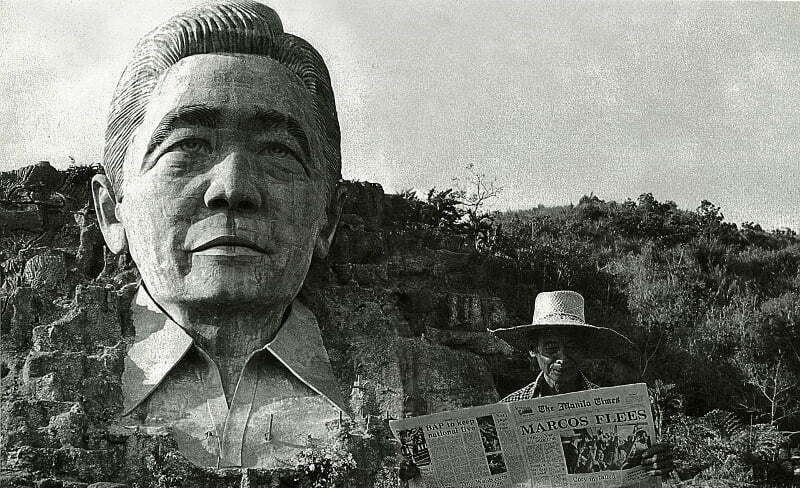 """A farmer in Agoo, La Union, standing in front of the Marcos monument, reads about it the following day in a newspaper carrying the headlines """"Marcos Flees."""""""