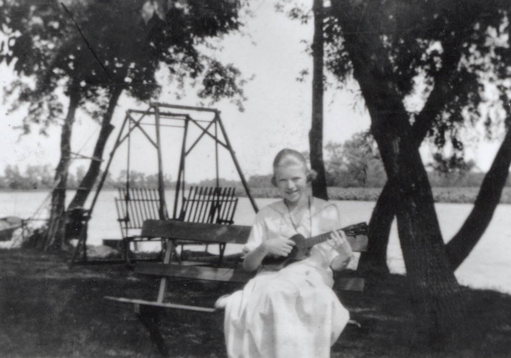 Lorine Niedecker playing the ukelele near the Rock River as a young woman. Photo courtesy of the Hoard Historical Museum. Click to enlarge.
