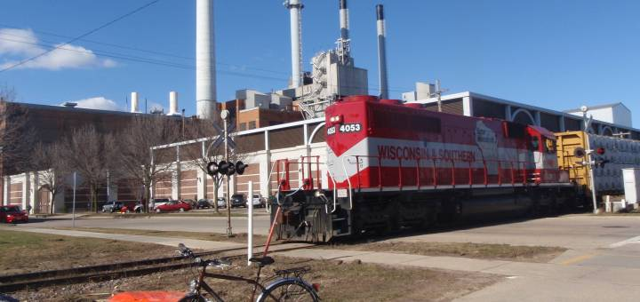 A Wisconsin and Southern locomotive engine passes in front of the Blount St. natural gas power plant in Madison, Wisconsin. A bicycle is parked in the foreground.