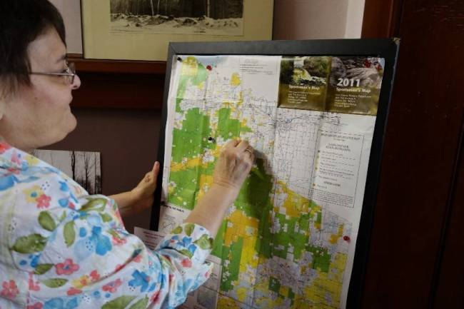 A woman who grew up in Iron County places a pin on a map collecting the favorite places of current and former residents. Photo by the author, August, 2016.