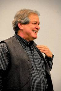 A man in a blue shirt and black vest holds his fingers to his shoulder while smiling.
