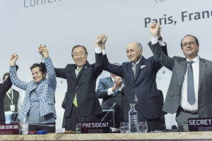 Closing ceremony of COP21, featuring Christiana Figueres (left), Executive Secretary of the UN Framework Convention on Climate Change and Secretary-General Ban Ki-moon (second from left) after the adoption of Paris Agreement on Climate Change. UN Photo, 2015.
