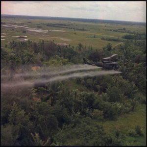 Helicopter sprays defoliation agent on forest during the U.S. war in Vietnam.
