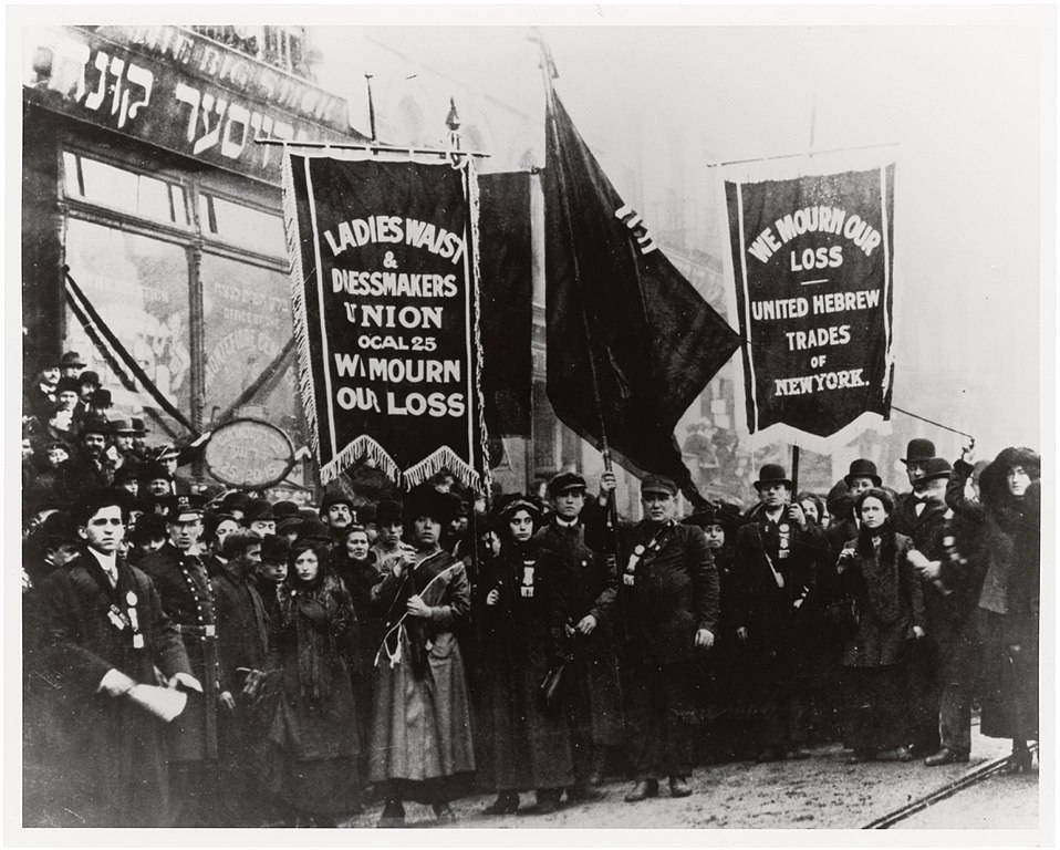 """A black and white photo of a crowd of fair-skinned, dark-haired people in winter clothing hold heavy fabric banners reading """"we mourn our loss"""" and the names of two unions--the """"Ladies Waist & Dressmakers Union Local 25"""" and """"United Hebrew Trades of New York"""". Behind them are storefronts, printed with Hebrew and English words."""