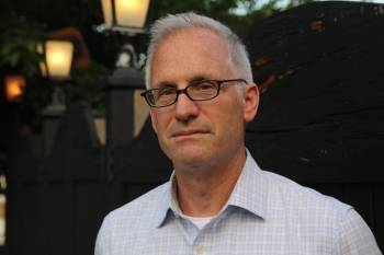 A photo portrait of a grey-haired man in an open-collar shirt wearing glasses and looking at the camera with a serious expression.