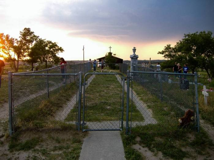 A metal fence in a cemetery lines the perimeter of a long patch of grass lines by a dirt footpath. The sun sets in the background.