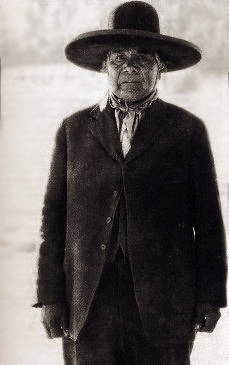 A Northern Paiute man poses with a wide-brimmed hat and formal dress.