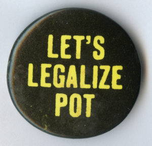 """A dark green circular button with yellow capital leaders reads """"Let's Legalize Pot"""""""