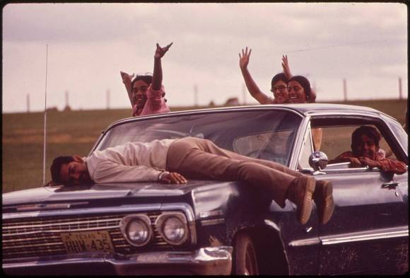 Six people lie on and sit in and on a blue sedan smiling at the camera, two raising their hands in the air, against a background of flat, green fields.