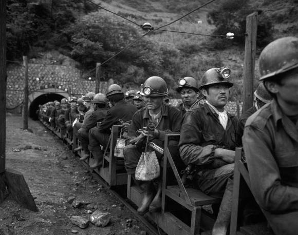 Picture showing men wearing helmets on a train at the entrance to a coal mine.