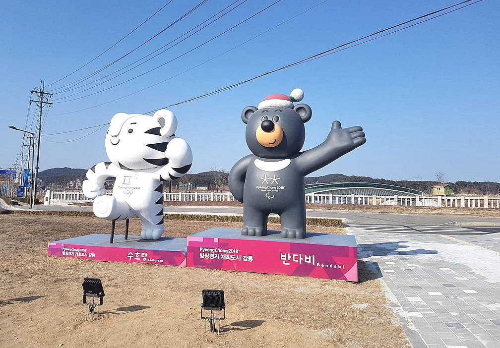 The mascots for the 2018 Winter Games, a white tiger, and the Paralympics, a black bear, welcome visitors outside one of the events.