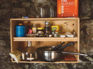 Cooking pots and canned food sit on shelves.