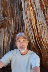 Michael Branch sits at the base of a tree.