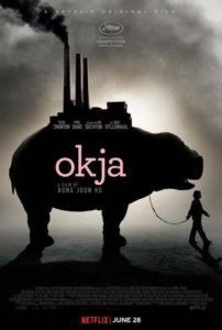 A black, white, and light pink film poster for Netflix's Okja showing a large porcine animal (with smokestacks seemingly growing out of it's back) being walked on a leash by the smaller shape of a young girl.
