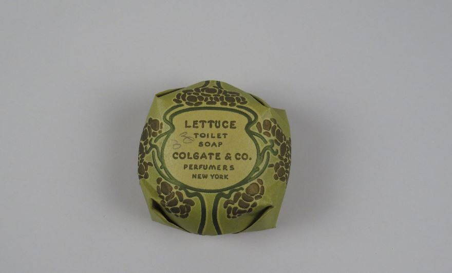 """An circular paper-wrapped olive-green package with a label that reads """"Lettuce toilet soap / Colgate & Co. / Perfumers / New York"""""""