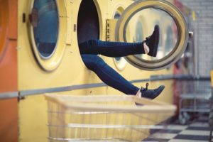 A woman's legs sticking out of a laundromat dryer.