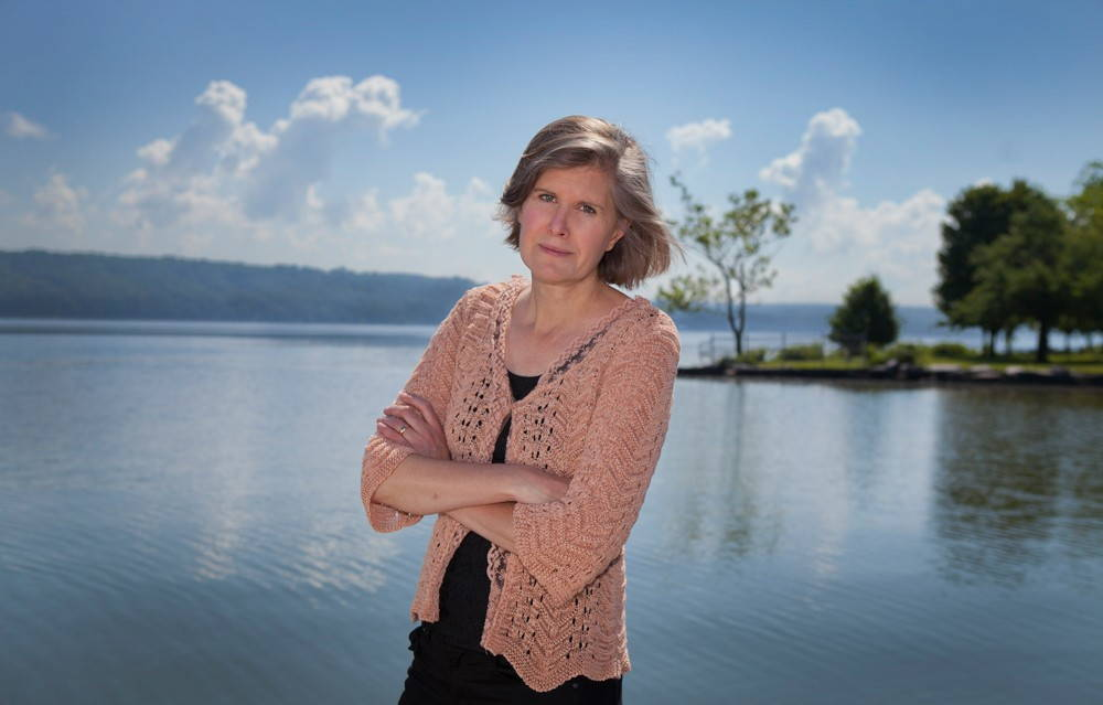 Sandra Steingraber stands in a lavender knit sweater, looking at the camera, in front of a placid lake.