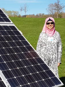 Huda Alkaff stands behind a solar array, angled down from left to right, wiht a green field and blue sky behind her.